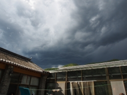 Dark storm clouds gather over the rooftops of our lunch hutong.