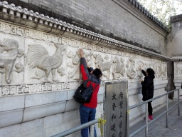 Visitors rubbing the carved zodiac signs on the screen walls, praying for good luck for themselves and their relatives.